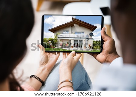 Couple Looking At House On Digital Tablet's Screen #1706921128