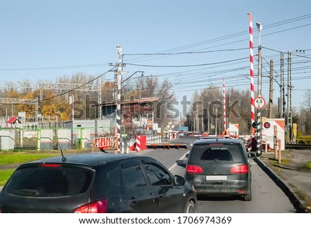 Cars in front of a railway crossing are stopped by raised barriers of protective devices on the road #1706974369