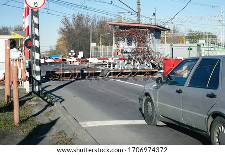 Car in front of a railway crossing with raised barriers of protective devices оn the road #1706974372