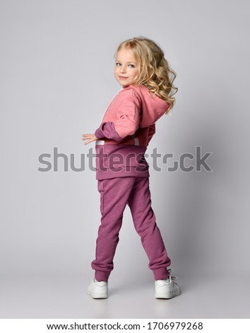 Full-growth portrait of curly blonde kid girl in stylish two-colored pink gray sportswear hoodie and pants posing back to us and turned to look at us over her shoulder