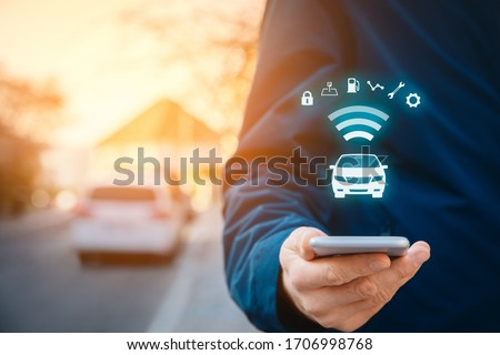Intelligent car app on smart phone concept, intelligent vehicle and smart cars concept. Person with smart phone on street, car in background and wireless communication with car. #1706998768