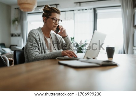 Businesswoman working on laptop computer sitting at home and managing her business via home office during Coronavirus or Covid-19 quarantine Royalty-Free Stock Photo #1706999230