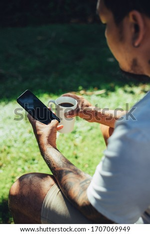 Mockup shot of man's hand with tattoos holding  cell phone and coffee cup with blank screen in backyard.