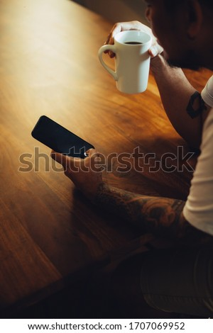 Mockup shot of man's hand with tattoos holding  cell phone and coffee cup with blank screen on desk at home office.