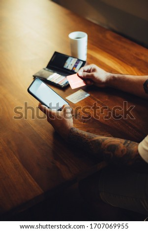 Mockup shot of man's hand with tattoos holding  cell phone and credit card with blank screen on desk at home office. For shopping.