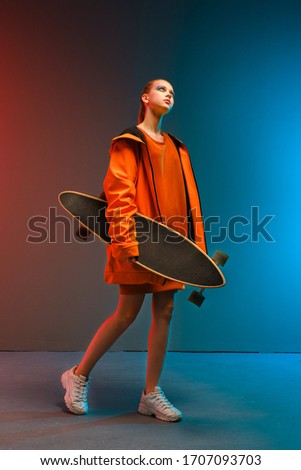 A young girl with bright makeup holds a longboard in her hands on a fashionable neon color background. Portrait of a girl skater. The concept of leisure, extreme sports, healthy lifestyle