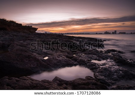 A stunning sunset from a rocky beach in Cabo de Palos with La Manga del Mar Menor in the background, Murcia, Spain