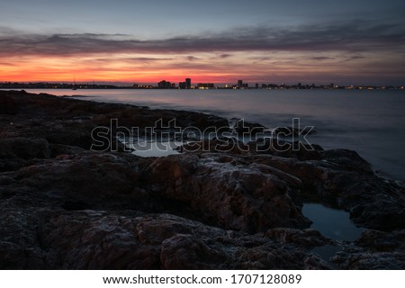 A stunning sunset from a rocky beach in Cabo de Palos with La Manga del Mar Menor starting to light up in the background, Murcia, Spain