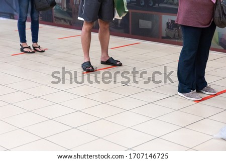 New normal lifestyle with social distancing where people are separated by a gap of at least 1 meter in queue into supermarket in Malaysia #1707146725
