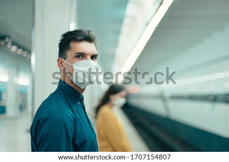 passengers in protective masks standing at a metro station at a safe distance #1707154807