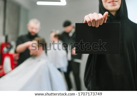 Barber in dark hoodie holds a card for copyspace on the background of a male hairdresser and barber clipping clients. Man holding blank black card, focus on blank space on barbershop background