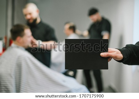 Barber holds a black blank card in his hand for copy space on the background of barbers clipping clients. Male hand holding a blank card on barbershop background.Barbershop advertising, place for text