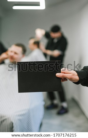 Male hand holding blank black card for copyspace on background of male hairdresser and barber clipping clients. Barber holds a dark blank card in hand on the background of a male hairdresser.Vertical