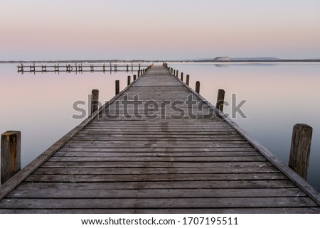Moody pier on the lake with beautiful sunset Royalty-Free Stock Photo #1707195511