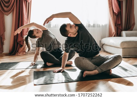 Young happy couple doing yoga on quarantine at home. Stretching, exercise, health Royalty-Free Stock Photo #1707252262