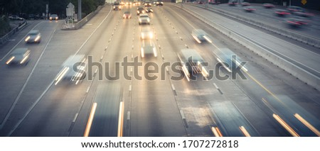 Busy frontage road and highway traffic in downtown Houston, Texas in rush hour. Long exposure slow motion cars commute on interstate highway at evening with light trail, high-occupancy vehicle lane