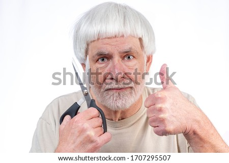 Horizontal shot of a gray haired man who's been in quarantine too long finally approves the haircut he gave himself with a thumbs up. Royalty-Free Stock Photo #1707295507