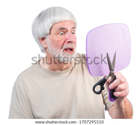 Horizontal shot of a gray haired man who's been in quarantine too long looking at the haircut he just gave himself. Royalty-Free Stock Photo #1707295510