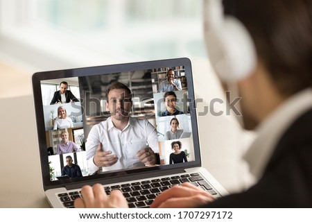 Different age and ethnicity diverse businesspeople participating at group videocall, laptop screen webcam view over man in headphones shoulder. Distant communication videoconference activity concept Royalty-Free Stock Photo #1707297172