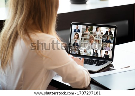 View over businesswoman shoulder sit at workplace desk looks at pc screen during group videocall with different age and ethnicity colleagues using application and webcam, distant communication concept #1707297181