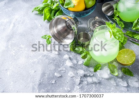 Basil smash gin alcoholic cocktail. Long alcohol drink recipe with fresh basil leaves and limes, grey stone background copy space Royalty-Free Stock Photo #1707300037