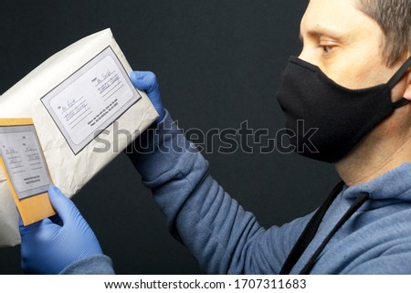 Delivery of correspondence during the period of self-isolation. A man in rubber gloves and a mask holds in his hands a delivered parcel and a letter.