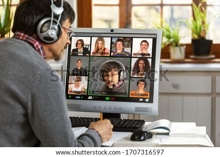 A moderator manages a video conference from his home office  #1707316597