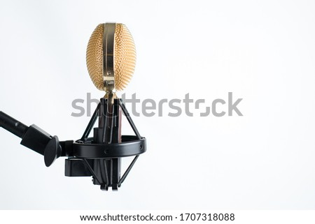 Gold colored microphone on vibration mount, isolated on white background.  Close-up of ribbon style microphone, with polished metal grill on black mic stand. Room for copy or text on right.