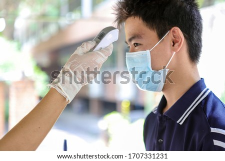 Public health personnel use non-contact infrared forehead infrared digital thermometers check fever of people to prevent spread of virus (Coronavirus, COVID-19) #1707331231