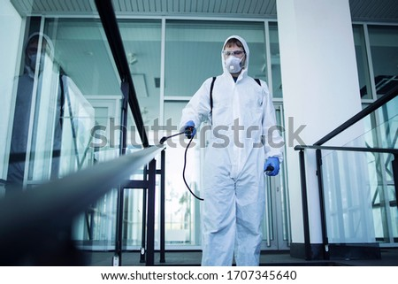 Shot of male person in white chemical protection suit doing disinfection of public areas to stop spreading highly contagious corona virus. Stop coronavirus or COVID-19. Royalty-Free Stock Photo #1707345640