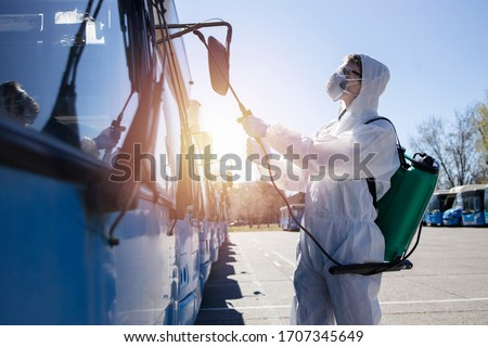 Public transport disinfection. Man in white protective suit with reservoir spraying disinfectant on parked buses. Stop coronavirus or COVID-19. #1707345649