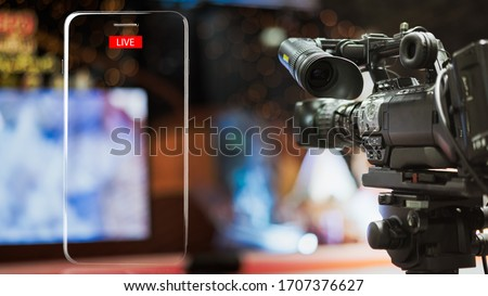 Video camera taking live video streaming with lighting frame of mobile phone and Live text at meeting room.