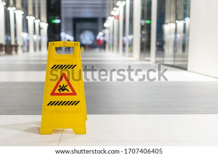 Slippery sign on wet floor in office building Royalty-Free Stock Photo #1707406405