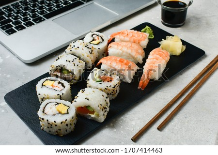 food delivery set of sushi and rolls with salmon and shrimp on a gray table next to a laptop. lunch at the computer. the concept of smart office. Top view of sushi, uramaki, hosomaki and nigiri.  #1707414463