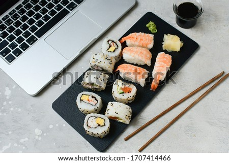 food delivery set of sushi and rolls with salmon and shrimp on a gray table next to a laptop. lunch at the computer. the concept of smart office. Top view of sushi, uramaki, hosomaki and nigiri.  #1707414466