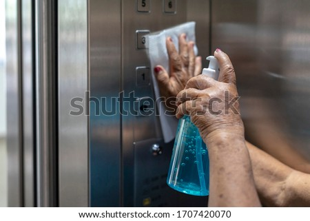 Close up women's hands spraying disinfectant from the bottle and wipe to clean an elevator push button control panel.Disinfection,cleanliness and heathcare,Anti bacterial and Corona virus ,COVID-19. #1707420070