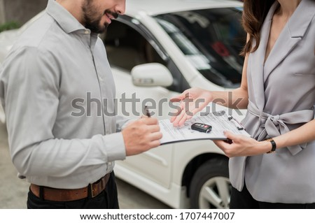 Automotive business, car sale or rental concept : Happy customer with car dealer agent making deal and signing on agreement document contract in auto showroom or car dealer office.