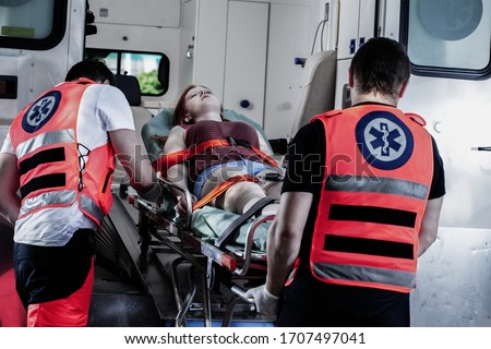 Female young victim of the accident lies on a stretcher in an ambulance #1707497041