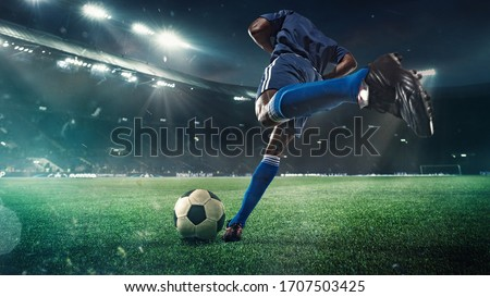 Professional football or soccer player in action on stadium with flashlights, kicking ball for winning goal, wide angle. Concept of sport, competition, motion, overcoming. Field presence effect. Royalty-Free Stock Photo #1707503425