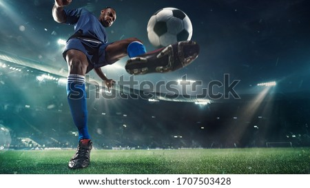 Professional football or soccer player in action on stadium with flashlights, kicking ball for winning goal, wide angle. Concept of sport, competition, motion, overcoming. Field presence effect. #1707503428