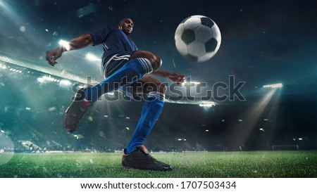 Professional football or soccer player in action on stadium with flashlights, kicking ball for winning goal, wide angle. Concept of sport, competition, motion, overcoming. Field presence effect. #1707503434