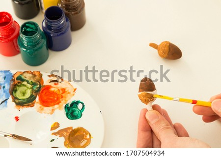The child is playing with stones from children's activities.kid painting acorn for her handcraft picture for nursery or kindergarten activity concept time.