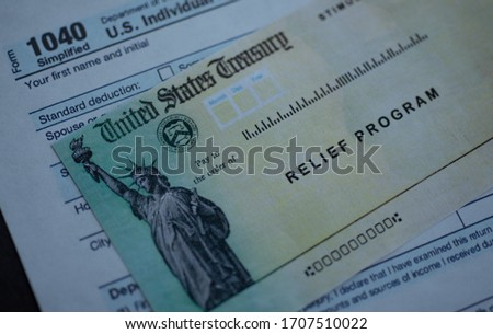Form 1040 U.S. Individual Income tax return next to the Stimulus Check Relief program. Close up view.  Royalty-Free Stock Photo #1707510022