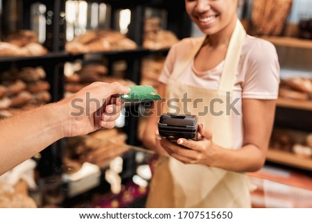 Retail trade concept. Cropped view of young adult man putting credit card to terminal, buying fresh bread in small family bakery