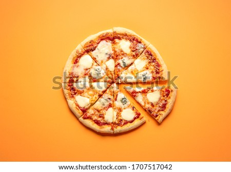 Sliced cheese pizza on an orange background above view. Pizza sliced in eight. Delicious homemade pizza top view. Pizza made only with cheese and tomato sauce. #1707517042