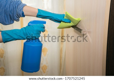 A girl in gloves disinfects the surface with a sanitizer antiseptic. Treats the door handle with an antibacterial agent. room antiseptic disinfection. Coronavirus prevention covid-19 2019-ncov #1707521245