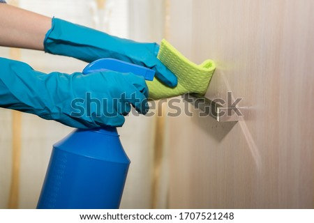 A girl in gloves disinfects the surface with a sanitizer antiseptic. Treats the door handle with an antibacterial agent. room antiseptic disinfection. Coronavirus prevention covid-19 2019-ncov #1707521248