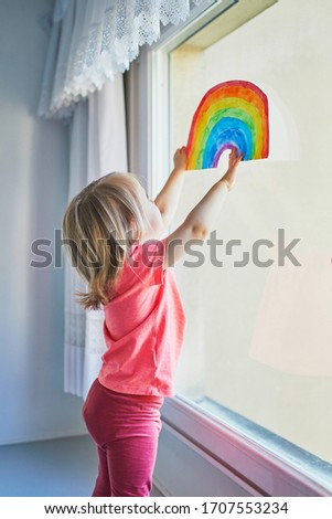 Adorable toddler girl attaching rainbow drawing to window glass as sign of hope. Creative games for kids staying at home during lockdown. Self isolation and coronavirus quarantine concept #1707553234