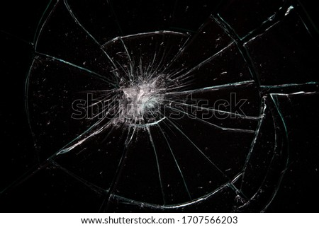 Broken glass with lots of cracks, studio shot with black background #1707566203
