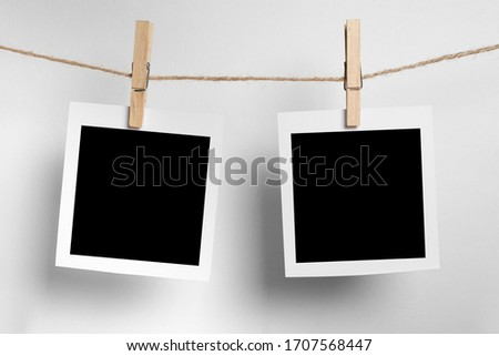 polaroid frame.Retro photo frames hanging on rope isolated on white background. real photo #1707568447
